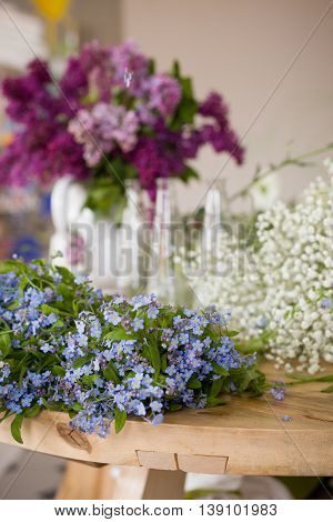 Beautiful spring and summer flowers on the table ready for bouquet. Many forget-me-not lilac blossoms on the wooden table. Flower decorations for home. Florist.
