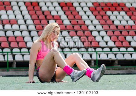 Woman athlete on the stadium. Fitness-woman make exercises.
