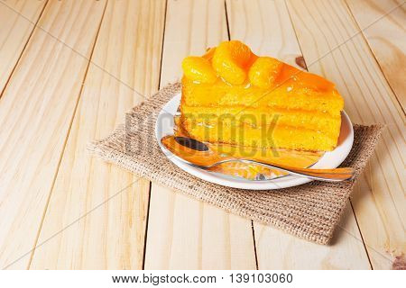 Orange fruit cake in a white plate on wooden table