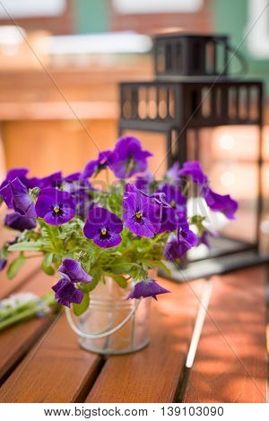 Beautiful pansy in a metal bucket as a table setting decoration. Nice flowers and a lantern on the wooden table outdoors. Summer cafe in the city.