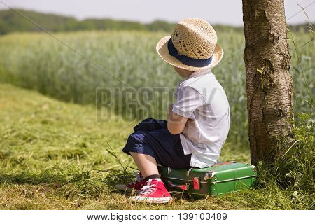Cute little kid boy in shorts white polo and straw hat sits on his green suitcase in a field near a tree waiting for a bus. summer portrait of a small child in profile retro style. Ready to travel.