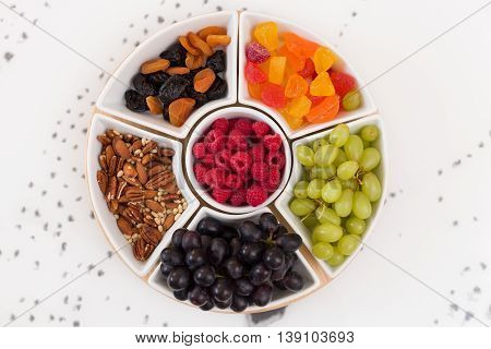 Round set of plates full of nuts raspberries sweets grapes and dry fruit on the white background. Healthy snacks. Desserts for coffee or tea. Assorted mix of pecans berries and fruit.