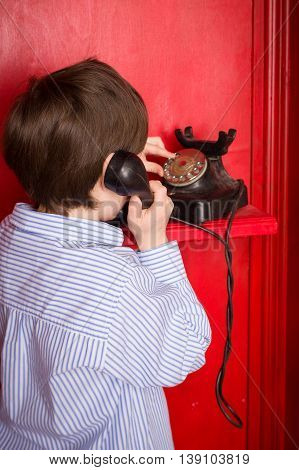 A boy in a blue shirt calling on the retro phone. Boy with an old telephone in the red phone booth in English style. Child with a black handset. Vintage telephone.