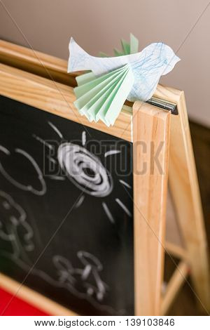 Paper bird on the chalk board in the kid's room. Origami bird made by a child. Bird decoration for child's room. Children drawings on the chalkboard.