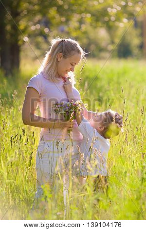 Cute little kid boy giving flower to his beautiful young mother on simmer day in the park. Outdoors. Together. Happiness. Family. Mom and son. Present for mother. Motherhood and childhood.