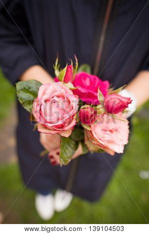 Closeup of woman's hand holding beautiful bunch of garden roses. View from above selective focus on flowers.