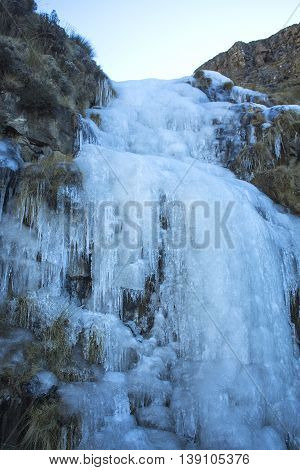 Frozen waterfall. Ice river. Sani Pass - mountain pass between the borders of South Africa and Lesotho. Winter in Africa. Natural phenomenon. Artistic retouching.