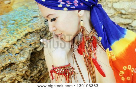 Portrait of a young woman wearing boho chic headband and handmade feathers necklace and earrings against stone backdrop