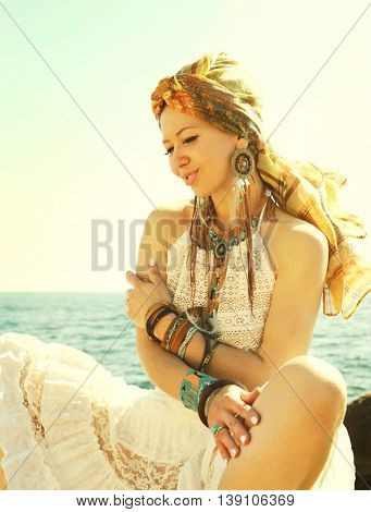 Hot african style fashion portrait of a beautiful young sitting  woman with headband, sunny backlit outdoor photo against seaside, boho chic style