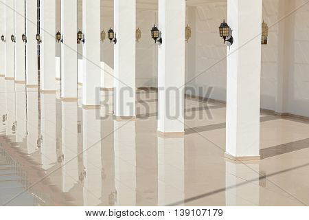 The columns of the building reflect on a smooth floor