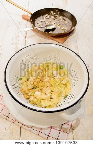 fried white cabbage and spring onions in a white colander