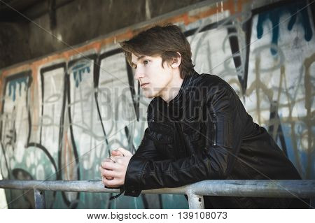A teenager depressed inside a dirty tunnel