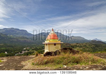 A small Hindu temple on-top of a hill in Kanthalloor overlooking the Western Ghats in the background, at Marayoor a village near Munnar, Kerala, India