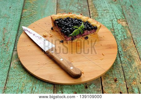 Last piece of homemade open pie decorated with fresh forest blueberries and knife on wooden board horizontal