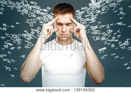 Brainstorming concept with pensive young man surrounded with abstract letters on grey background