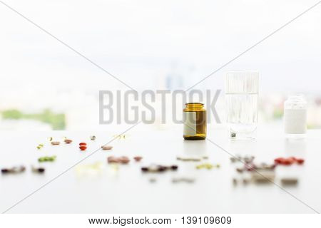 Closeup of blurry white table with colorful pills and capsules medicine bottles and a glass of water. Selective focus