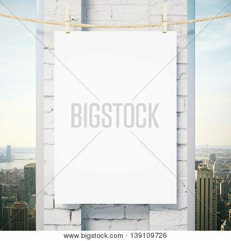Blank poster hanging outside on rope with pegs. White brick column and city view in the background. Mock up 3D Rendering