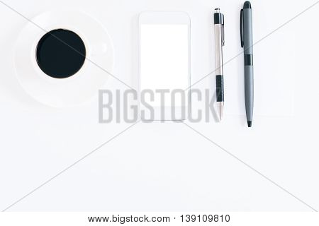 Top view of white desktop with coffee cup blank mobile phone and pens. Mock up