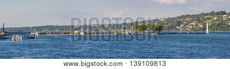 Geneva Switzerland - July 15 2016: Panoramic view of the popular Bains des Paquis an artificial peninsula on lake Geneva it features a public bath a restaurant and a lighthouse at the tip of the jetty.