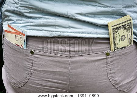 Two kinds of currency in rear trouser pockets