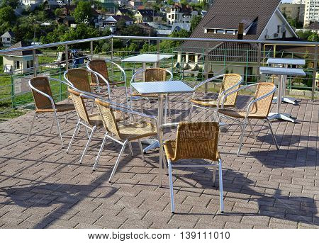 Wicker chairs with metal legs and racks are in an open cafe area