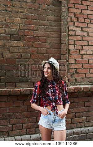 The girl tourist standing and holds hands in pockets against the wall of red brick