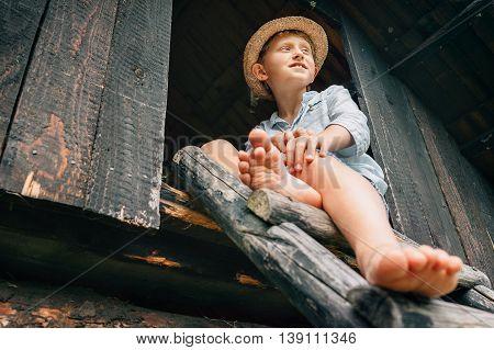 Barefoot boy sits on ladder in barn attic