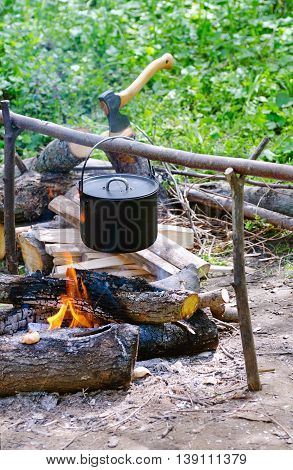 Tourist pot of water hanging over a fire of wood in the Camping.