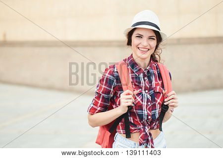 Portrait of a cheerful girl tourist with hat in town