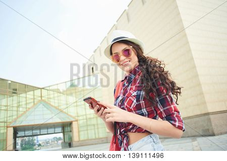 Portrait of a girl tourist in a hat, sunglasses and mobile phone in hand on the background of the building with glass facades