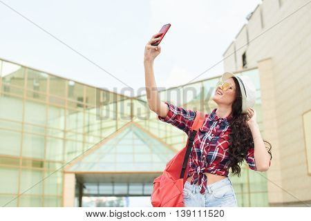 Girl tourist makes selfie in the city on the background of the task with a glass facade