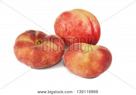 Nectarine and two flat peaches on white background