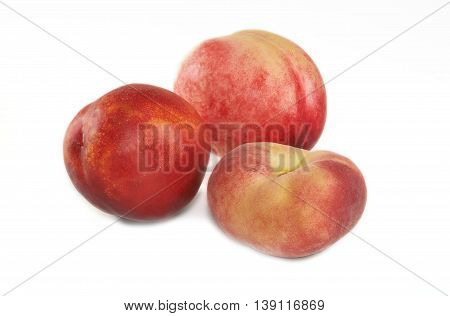 Two nectarines and flat peach on white background