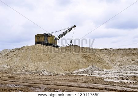 Working digger in a quarry produces sand. Working digger in a quarry produces sand