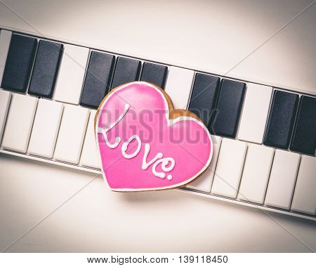 Love heart on Music keyboard for valentines and music love. Pink Music cookie heart on white background.