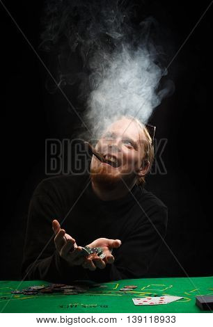 Beautiful young red-haired man with fuming cigar in shirt with long sleeves sitting at poker table and enjoys win holding chips in hands at black background.