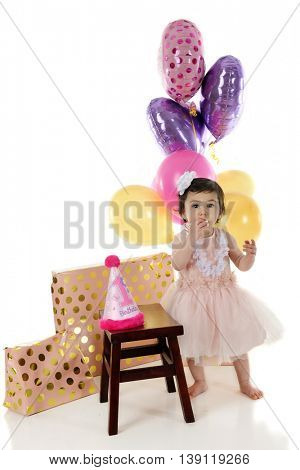 An adorable baby girl eating the #1 candle from her first birthday cake.  On a white background.
