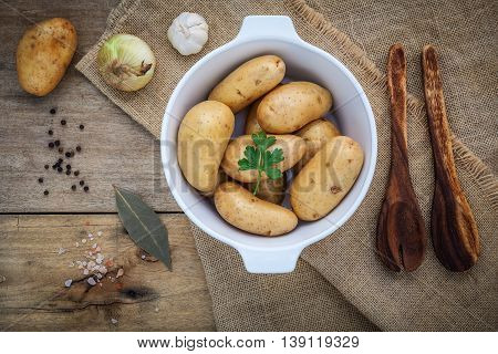Fresh Organic Potatoes In White Ceramic Bowl With Ingredients And Herbs  , Parsley, Garlic, Bay Leav