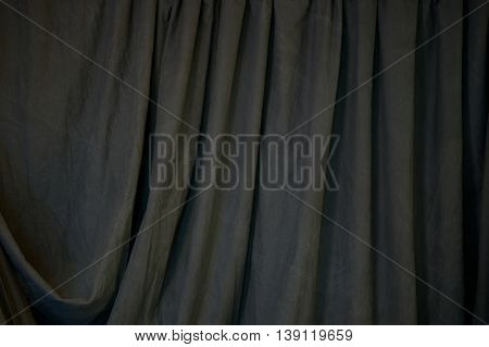 A black draped backdrop cloth fills the image with vertical folds.
