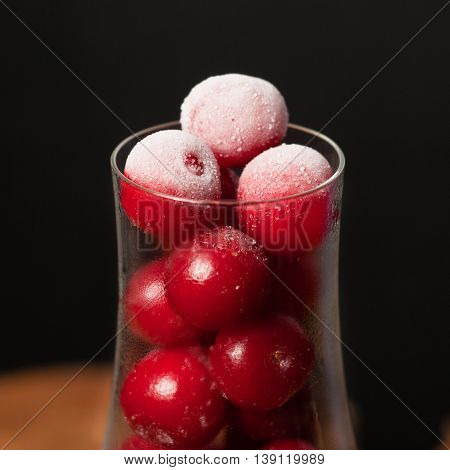 Frozen cherry in the wine glass, chilled berry on wooden table