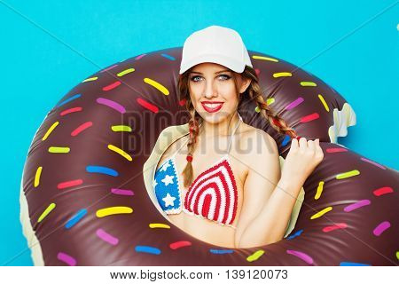Cool young blonde Caucasian woman in American flag crochet bikini top, with brown inflatable donut float with colorful sprinkles. Modern beautiful teenage girl in summer beach style. Medium retouch