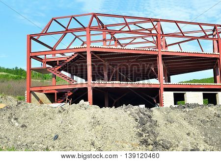 Metal construction building under construction and building sand against the blue sky