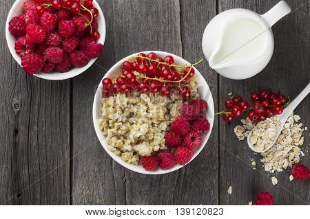 Oatmeal with raspberry and red currant on a wooden background