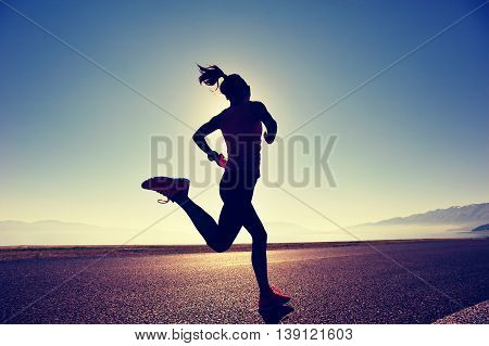 healthy lifestyle young woman runner running on sunrise seaside