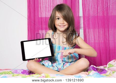 The technologies become easier. Cute little girl holding digital tablet