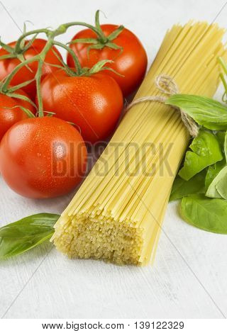 Ingredients for paste: spaghetti, basil and tomatoes on a white background.