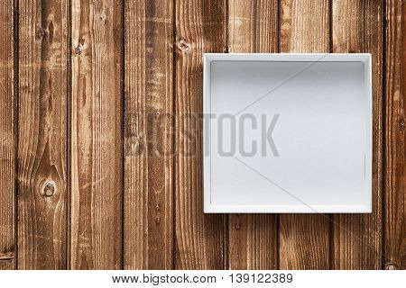 Open cardboard box on wooden background top view