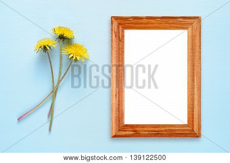 Dandelion flowers and photo frame on turquoise background