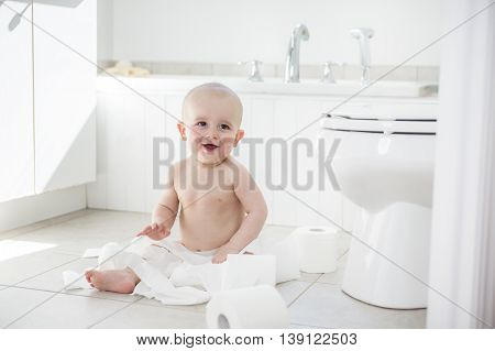 An Adorable baby boy playing with toilet paper
