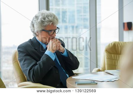 Mature business man works with docs in modern office
